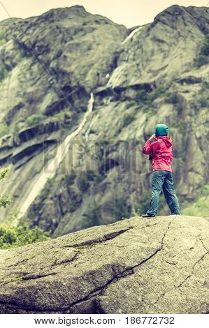 Woman on mountain rock enjoying beautiful nature view. Adventure and traveling concept.