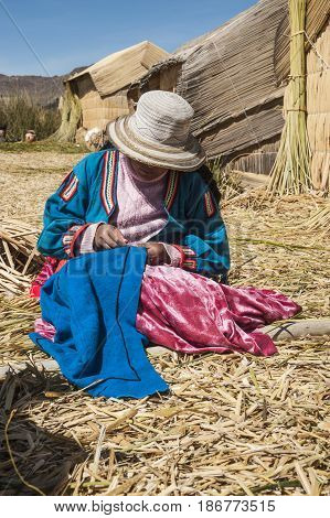 Uros Floating Islands Titicaca Peru - 30 July 2011: Unrecognizable woman in national costume of Indian Uros is embroidering a decorative pillow