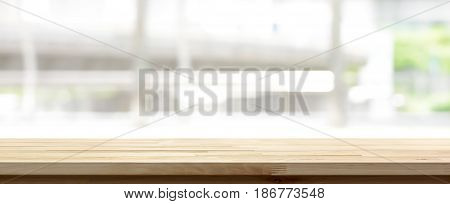 Wood table top on blur kitchen window background panoramic banner - can be used for display or montage your products (food)
