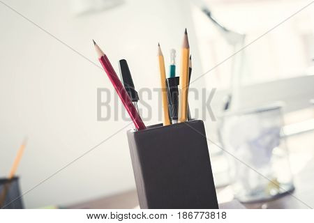 Office supplies pencils and markers in pen holder on working desk