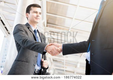 Businessmen making handshake at outdoor covered walkway - greeting dealing merger and acquisition concepts