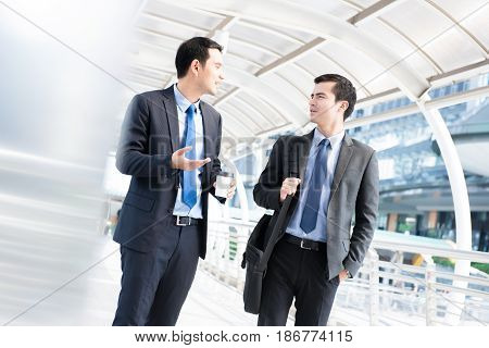 Interracial businessmen as colleague walking and talking in the morning at outdoor covered walkway