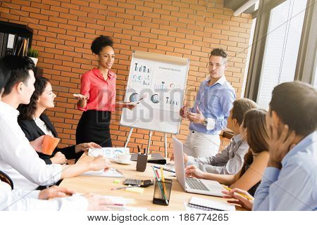 Mixed race business people in meeting room making a presentation