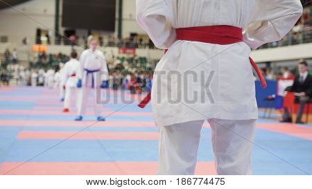 The athlete stands in a white kimono with a red belt preparing for a fight with an opponent in a white kimono with a blue sash and blue fighting gloves. For springa watching the judge in a black suit with a red flag. Competitions in karate among young ath