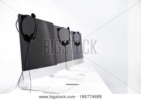 Microphone headsets hanging on computer monitors in call center