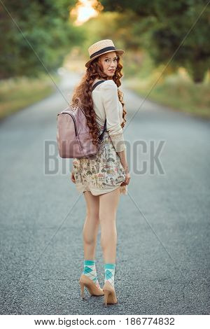 Young girl traveler enjoy the travel on foot. Happy woman walking with hat and backpack on the road and looking at camera. Adventure is coming concept