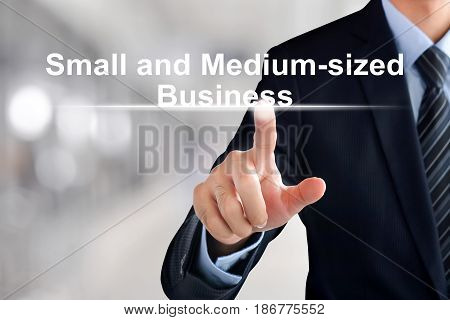 Businessman hand touching Small and Medium-sized Business (or SMB) text on virtual screen