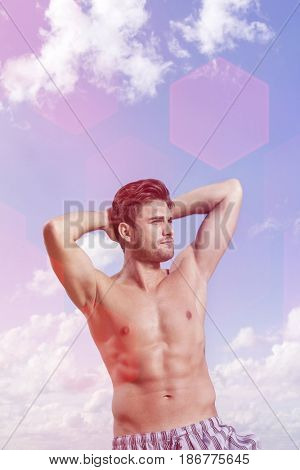 Young muscular man with hands behind head against cloudy sky