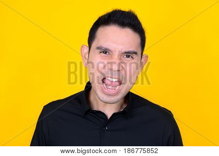 Asian man feeling angry and frustrated on yellow background
