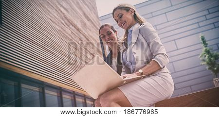 Businesswomen sitting and using laptop in office premises