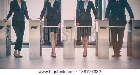 Businesspeople standing at turnstile gate in office