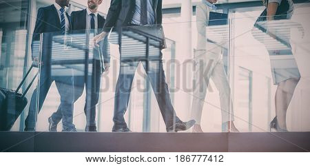 Businesspeople holding suitcase walking in office