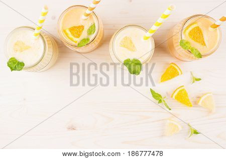 Decorative border of orange and yellow lemon smoothie in glass jars with straw mint leaf top view. White wooden board background copy space.