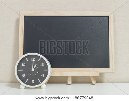 Closeup alarm clock for decorate show 1 o'clock with wood black board on white wood desk and cream wallpaper textured background selective focus at the clock
