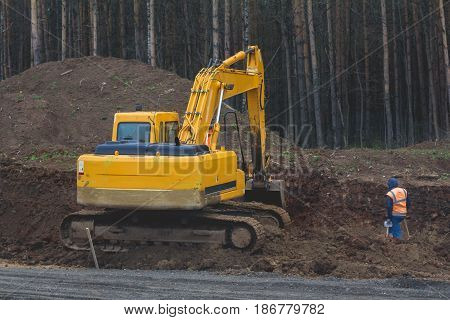 Construction of the highway - yellow excavator at work, telephoto
