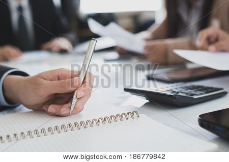 Businessman hand holding pen on the table in the meeting selective soft focus