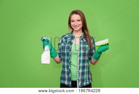 Housework and housekeeping concept. Spring cleaning. Cleaning woman with cleaning spray bottle brush and gloves happy and smiling. Beautiful cleaning girl isolated on green background with copyspace. Mixed race woman.