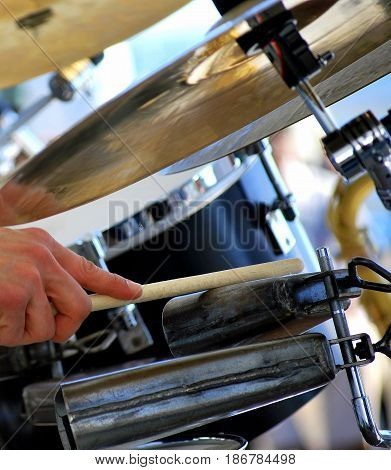 Latin jazz drummer performing a solo in concert outdoors.