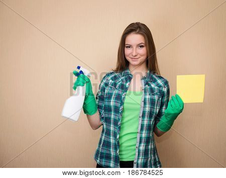 Housework and housekeeping concept. Young woman with cleaning spray bottle happy and smiling. Spring cleaning. Beautiful cleaning gir.