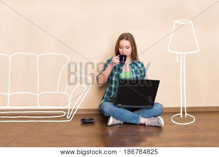Happy young woman sitting on the floor with crossed legs using laptop and drinking coffee in empty room with sketched furniture. Young girl in the new flat. Beautiful girl working in empty apartment.