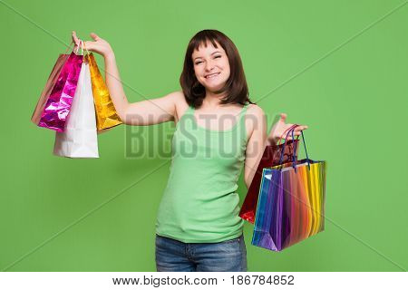 Happy young girl with colorful shopping bags isolated on green background. Shopper. Sales.