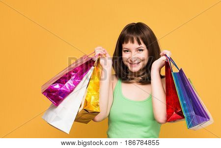 Sales. Shopper. Happy young girl with colorful shopping bags isolated on yellow background.