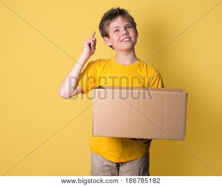 Boy thinking holding a box on yellow background. Think out of the box concept.