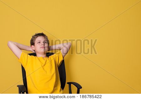 Portrait of happy teen boy in yellow t-shirt looking upwards in thought relaxing isolated on yellow wall background.