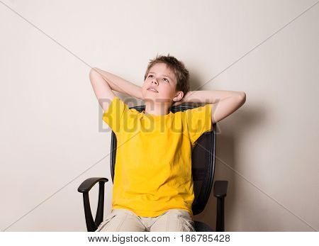 Portrait of happy teen boy in yellow t-shirt sitting on a chair with arms in the head looking upwards in thought relaxing.