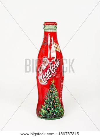 DAYTON, OHIO, USA - JANUARY 28, 2017: Coca-Cola often produces Special Edition Bottles. This 2002 Classic features Santa drinking a Coke with a Christmas tree at bottom of bottle, isolated on white.