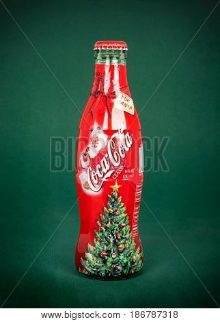 DAYTON, OHIO, USA - JANUARY 28, 2017: Coca-Cola often produces Special Edition Bottles. This 2002 Classic features Santa drinking a Coke with a Christmas tree at bottom of bottle, isolated on green.