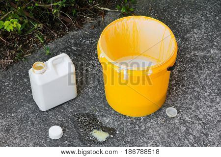 paint bucket yellow and a gallon on the cement floo
