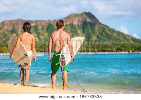Hawaii surfers people relaxing on waikiki beach with surfboards looking at waves in Honolulu, Hawaii. Healthy active lifestyle fitness couple at sunset with diamond head mountain in the background.