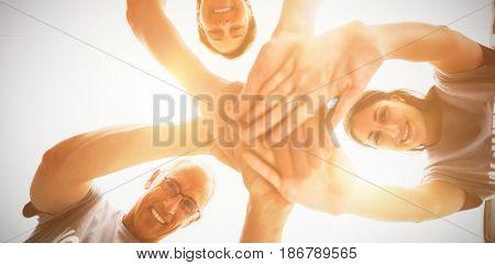 Portrait of happy volunteers stacking hands together