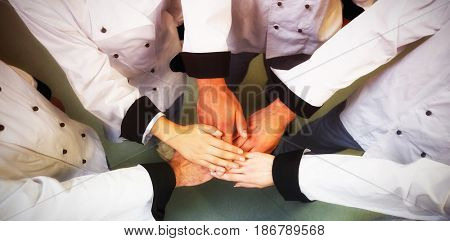 High angle view of chef stacking hands while standing in kitchen