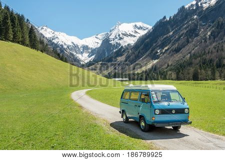 OBERSTDORF, BAVARIA, GERMANY - MAY 10, 2017: Vintage blue and white VW Bully camping car driving on mountain valley road in Trettachtal valley, Allgauer Alps.
