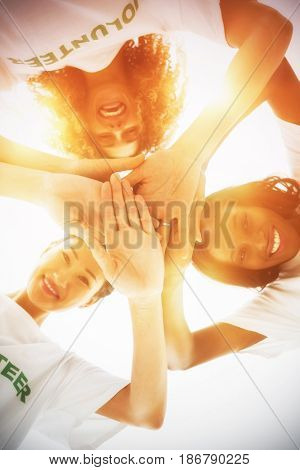 Directly below shot of volunteers stacking hands while standing against white background
