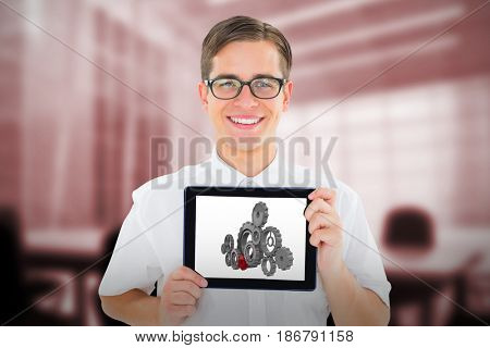 Geeky businessman showing his tablet pc against computer generated image of empty board room