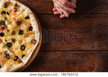 Hot yummy italian pizza served on wooden background, flat lay with free space for text. Italian cuisine. Unrecognizable person hands on rustic dark table.