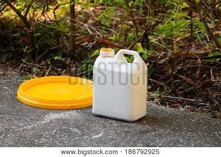 white plastic gallon of oil for color combinations on the cement floor