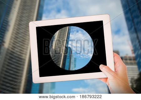 Masculine hand holding tablet against city