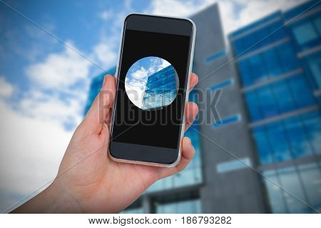 Hand holding mobile phone against white background against low angle view of office building