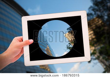 Masculine hand holding tablet against residential buildings against sky
