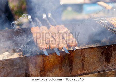 Man frying shish kebab on an open fire in the street
