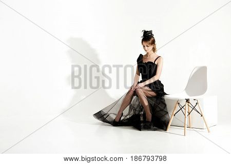 fashion shot of elegant sad woman in a black dress and veil sits on a chair and waiting on white background