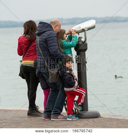 LAZISE ITALY - APRIL 30 2016: The family ooks in a stationary telescop at Garda Lake. Italy