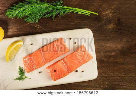 Two slices of salmon on a dark background with a place for text, with slices of lemon, peppercorns, and dill sprigs, shot from above