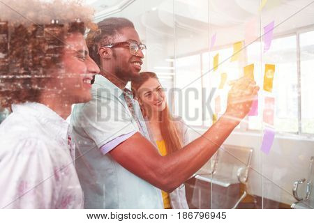 High angle view of illuminated cityscape against creative bussiness people discussing over adhesive notes