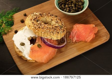 A photo of a bagel with cream cheese and lox, with a purple onion ring, a sprig of dill, and capers, shot on a black texture with a place for text