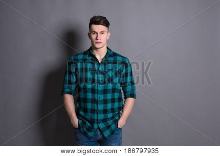 Young handsome man studio portrait. Boy style, trendy hipster in checkered shirt look with cool hairstyle